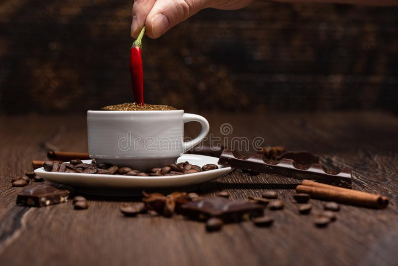 A pod of red hot pepper in a cup of black coffee. Coffee beans, chocolate, star anise on a wooden background. royalty free stock photography