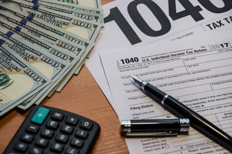Podatek forma 1040, pióro, dolary, kalkulator na stole zdjęcia stock