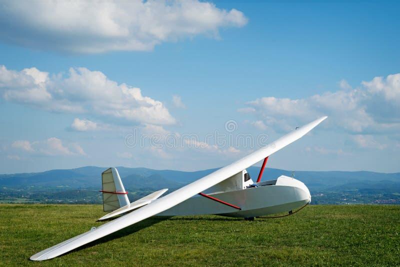 Podbij świat, słoneczny dzień, niebieskie niebo, na zielonym polu stoi biały szybowiec gotowy do lotu zdjęcie stock