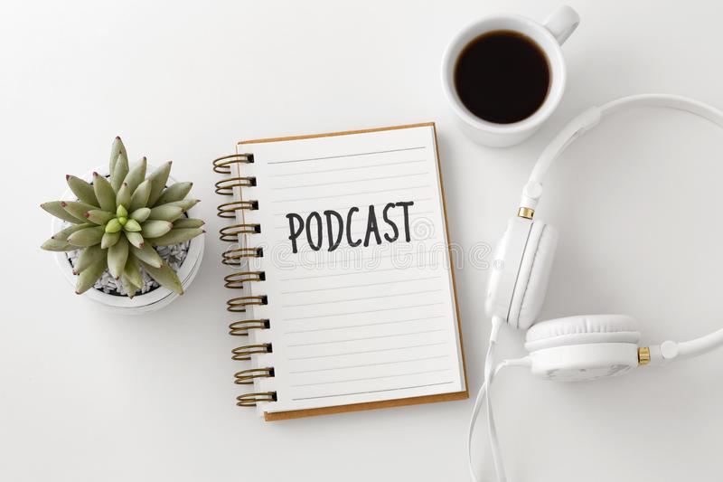 Podcast word on notebook with headphones. Podcast concept with headphones, notebook and coffee cup on white desk, top view royalty free stock photography