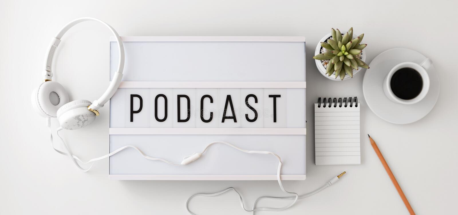 Podcast concept with headphones, notepad on white background, flat lay stock image