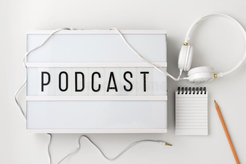Podcast concept with headphones, notepad on white background, flat lay royalty free stock photo