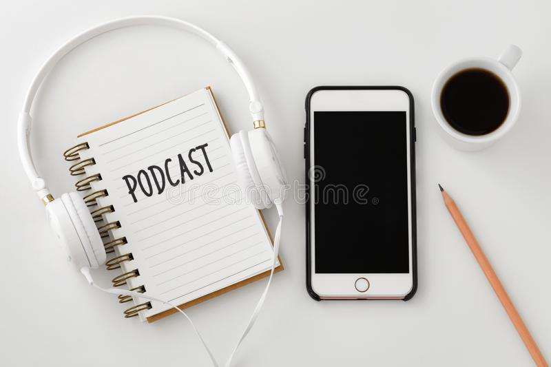 Podcast concept with smartphone and headphones. Podcast concept with headphones and smartphone on white table, flat lay stock images