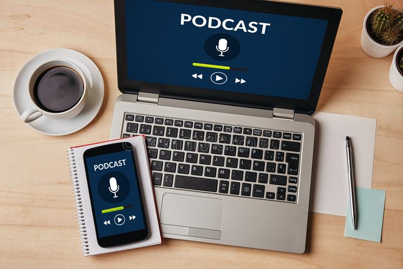 Podcast concept on laptop and smartphone screen over wooden tabl. E. All screen content is designed by me. Flat lay stock images