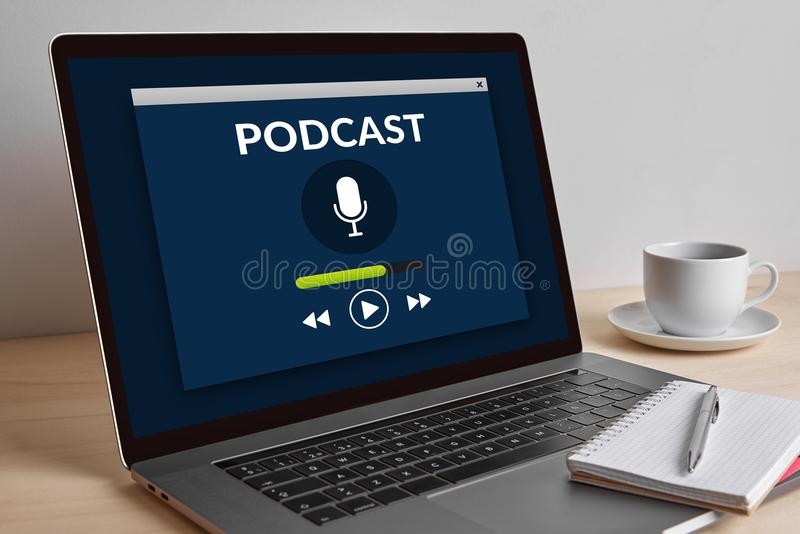 Podcast concept on modern laptop computer screen on wooden table. All screen content is designed by me royalty free stock image