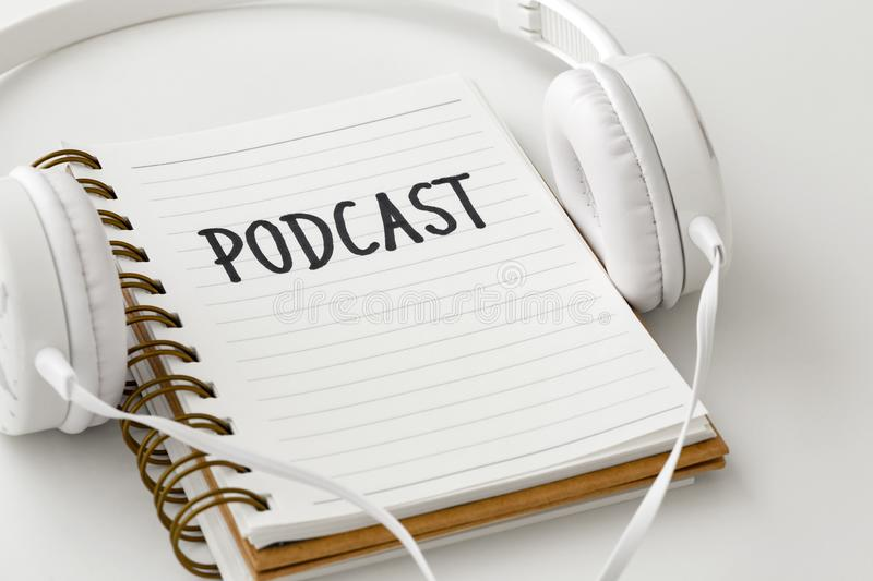 Podcast concept. With headphones and podcast word on notebook on white background royalty free stock photos