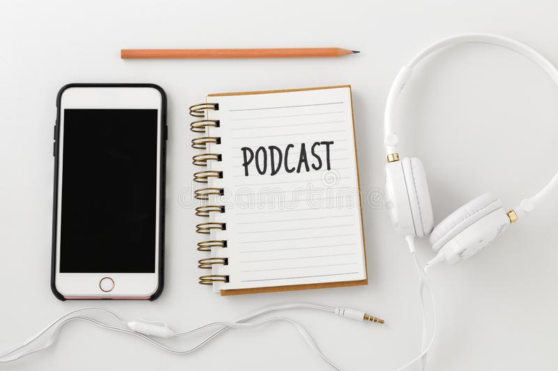 Podcast concept with smartphone. Podcast word on notebook with smartphone and headphones on white desk, top view stock image