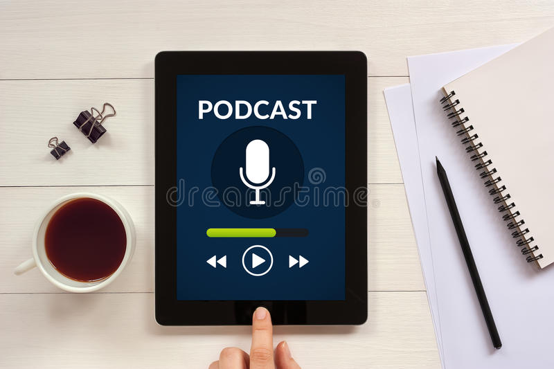 Podcast concept on tablet screen with office objects. On white wooden table. All screen content is designed by me. Flat lay royalty free stock photos