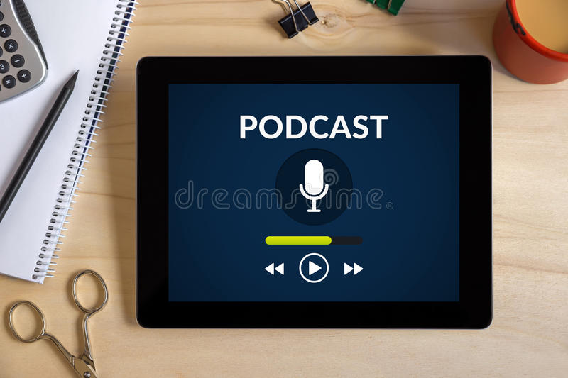 Podcast concept on tablet screen with office objects on wooden d. Esk. All screen content is designed by me. Top view stock photo