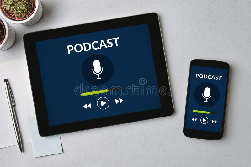 Podcast concept on tablet and smartphone screen. Over gray table. All screen content is designed by me. Flat lay stock image