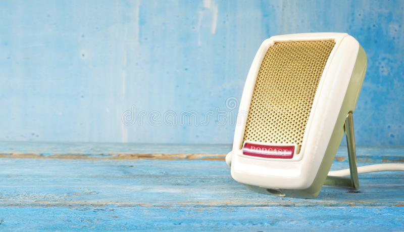 Podcast concept, vintage microphone close up , grungy blue background, panorama,copy space stock images