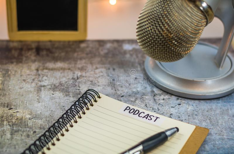 Podcast idea concept with microphone and notebook on gray table. Podcast idea concept with microphone, notepad and tablet on table. Ideas, plans, topics for royalty free stock image