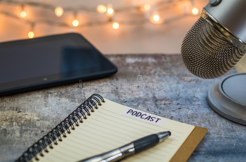 Podcast idea concept with microphone and notebook and tablet on gray table. Podcast idea concept with microphone, notepad and tablet on table. Ideas, plans stock image