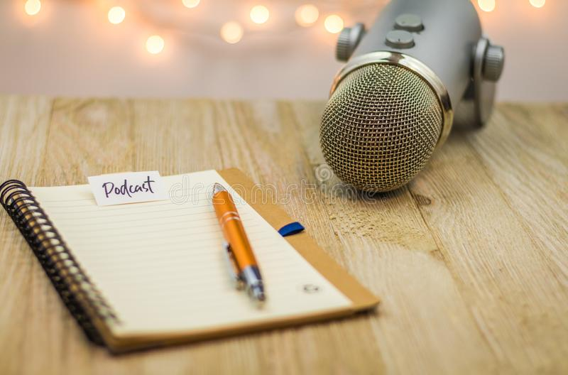 Podcast idea concept with microphone and notebook on wooden board. Podcast idea concept with microphone, notepad and tablet on table. Ideas, plans, topics for royalty free stock photography
