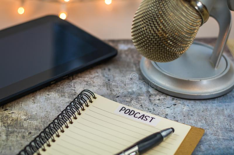 Podcast idea concept with microphone and notebook and tablet on gray table. Podcast idea concept with microphone, notepad and tablet on table. Ideas, plans stock images
