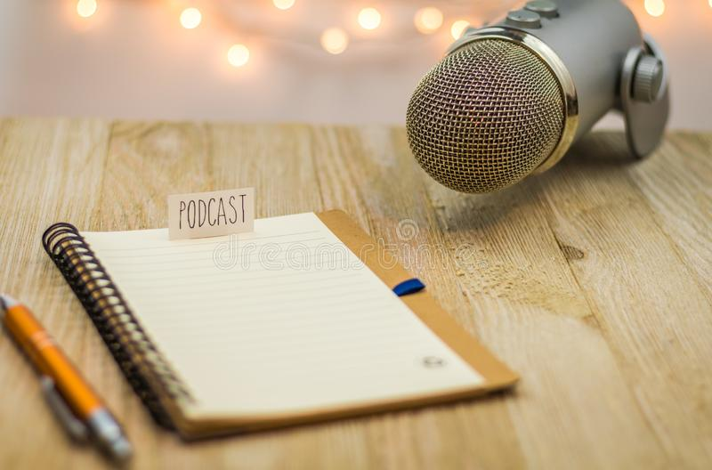 Podcast idea concept with microphone and notebook on wooden board. Podcast idea concept with microphone, notepad and tablet on table. Ideas, plans, topics for stock photography