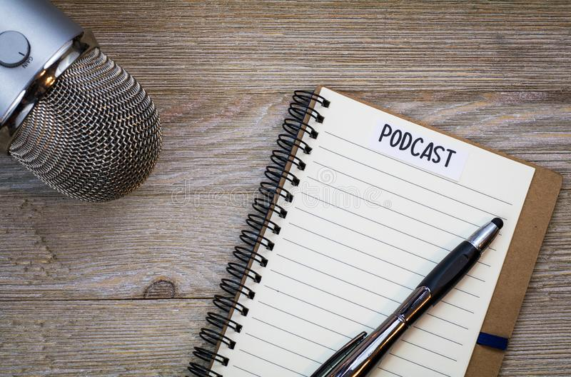 Podcast idea concept with notebook and mic on wooden board, flat lay. Podcast idea concept with microphone, notepad and tablet on table. Ideas, plans, topics for stock image