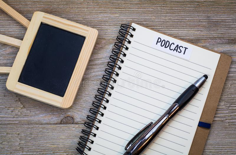 Podcast idea concept with notebook on wooden board, flat lay. Podcast idea concept with microphone, notepad and tablet on table. Ideas, plans, topics for Podcast stock photography