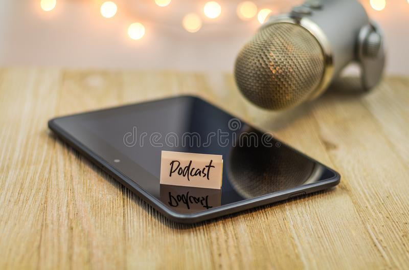 Podcast idea concept with microphone and shiny black tablet on wooden table. Podcast idea concept with microphone, notepad and tablet on table. Ideas, plans stock photography