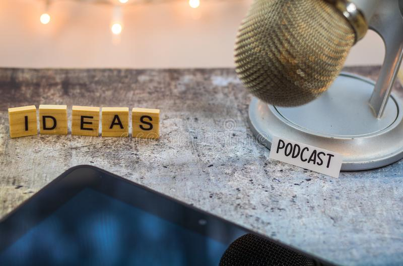 Podcast idea concept with microphone,and tablet on table. Podcast idea concept with microphone, notepad and tablet on table. Ideas, plans, topics for Podcast royalty free stock photography