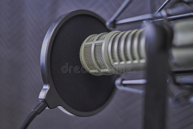 Podcast microphone closeup in a recording booth. Closeup shot of a dynamic microphone in a recording booth with a wind screen stock photos