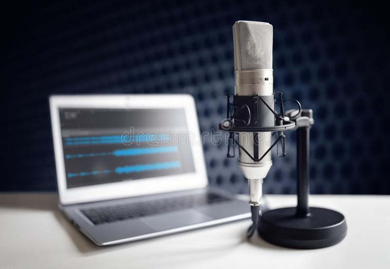 Podcast microphone and laptop computer in recording studio stock photography