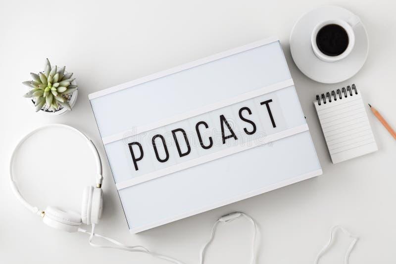 Podcast ordet på lightbox med hörlurar på den vita tabellen arkivfoto