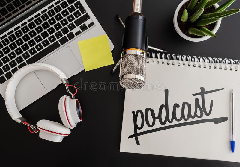 Podcast recording concept with microphone, headphones and laptop computer next to note pad stock images