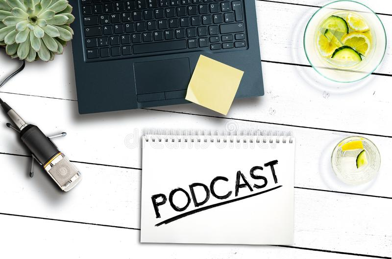 Podcast recording concept with laptop computer and microphone on rustic wooden table royalty free stock image