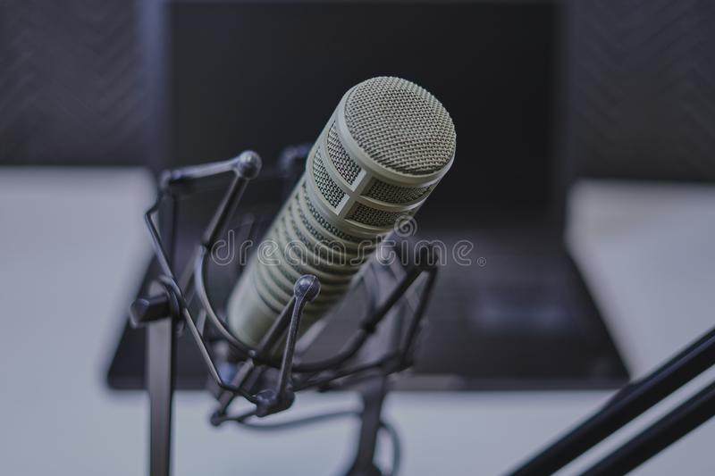 Podcast microphone with laptop computer in background stock photo
