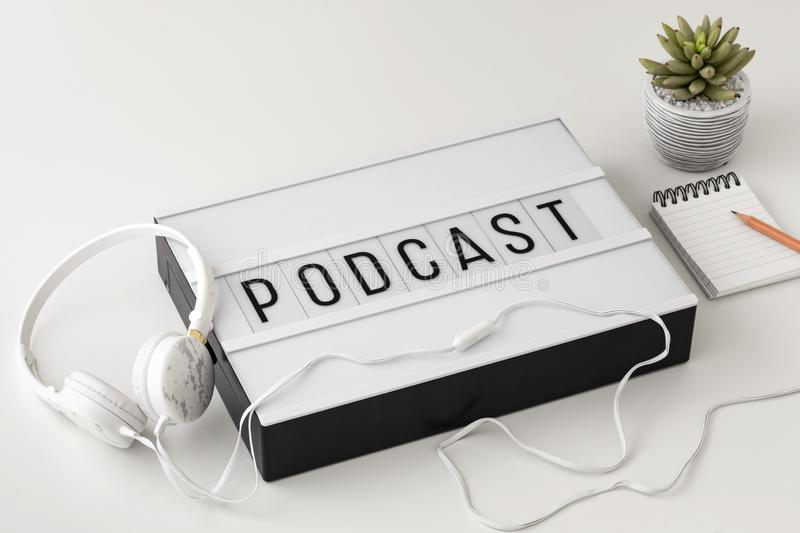 Podcast word on lightbox with headphones and notepad on white background. Podcast concept stock photography