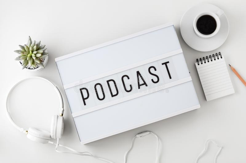 Podcast word on lightbox with headphones on white table stock photo