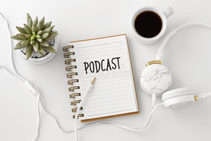 Podcast concept with headphones and notebook. Podcast word on notebook with headphones and coffee cup on white desk, flat lay stock image