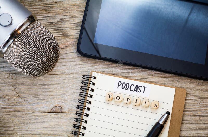 Podcastidébegrepp med anteckningsboken, mic och minnestavlan på träbrädet, plan la royaltyfri bild