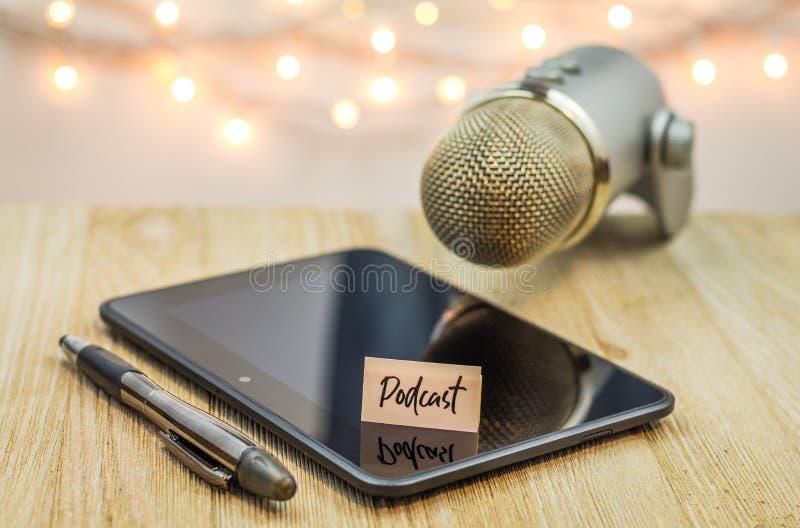 Podcastidébegrepp med mikrofonen och den skinande svarta minnestavlan på trätabellen arkivfoto