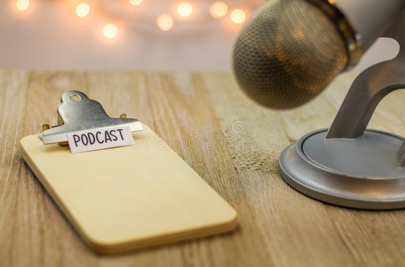 Podcastidébegrepp med mikrofonen och skrivplattan royaltyfri fotografi