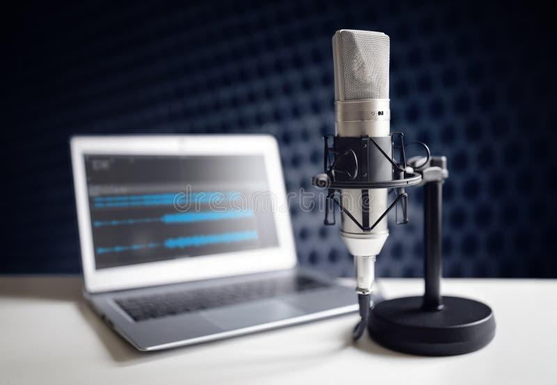 Podcastmikrofon och bärbar datordator i inspelningstudio arkivbild