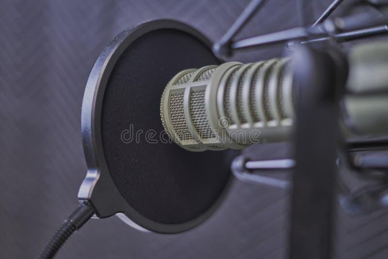 Podcastmikrofoncloseup i ett anteckna bås arkivfoton