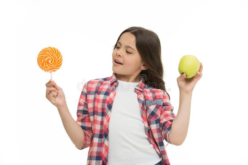 Pode adoçar o gosto doce fazem-nos felizes A menina guarda o pirulito e a maçã doces Alternativa do almoço escolar A menina escol foto de stock