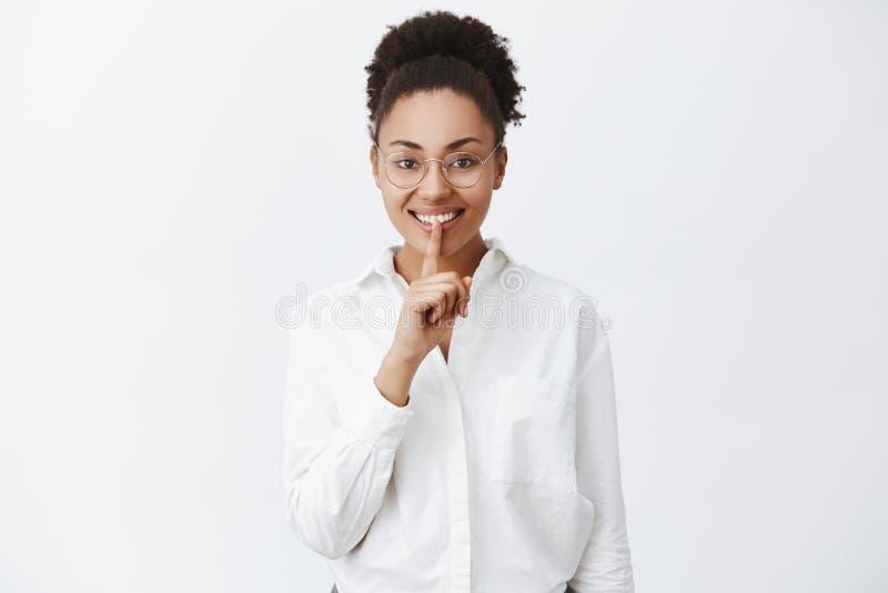 Pode você manter segredos Chefe fêmea afro-americano excitado alegre nos vidros e na camisa branca, vindo em casa tarde, pedindo imagem de stock