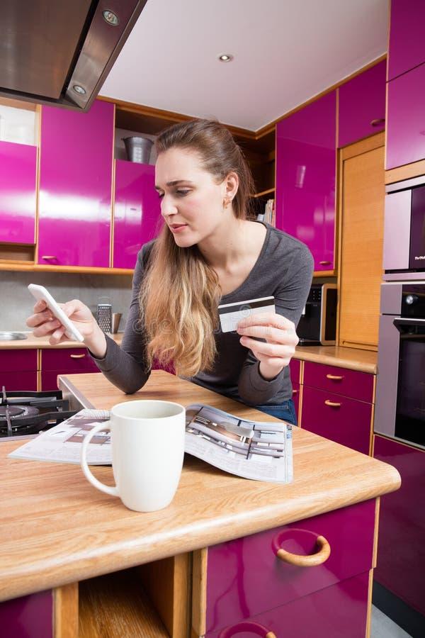 Podejrzana młoda kobieta używa jej telefon komórkowego dla handlu elektronicznego obraz stock