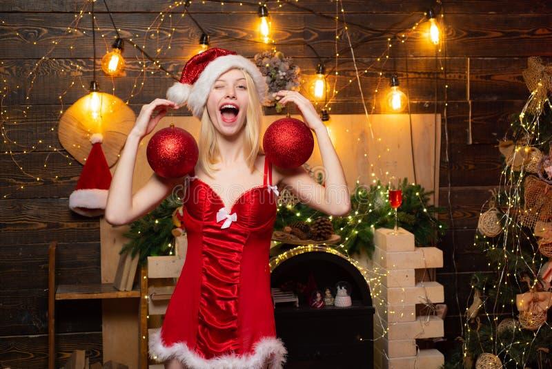 Podekscytowana i seksowna blondynka w czerwonej bieliźnie, pokazująca świąteczne jaja Świętująca partia noel Boże Narodzenie fotografia royalty free