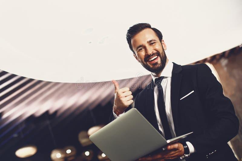 Podekscytowany młody człowiek z laptopem podnoszącym kciuk i uśmiechającym się obrazy royalty free