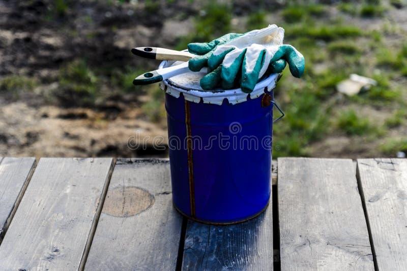 poder de la pintura que miente en la terraza de una casa privada con un cepillo y los guantes, lista para ser abierto y para ser  imagen de archivo