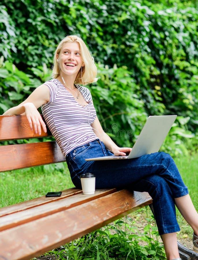 Poder de las llamadas de la naturaleza Trabajo de la muchacha con el ordenador portátil en parque Oficina del ambiente natural Ra fotos de archivo