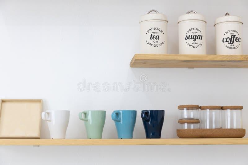Poder del metal de la taza del café o del té y de cristal en estante de madera con la pared blanca fotos de archivo