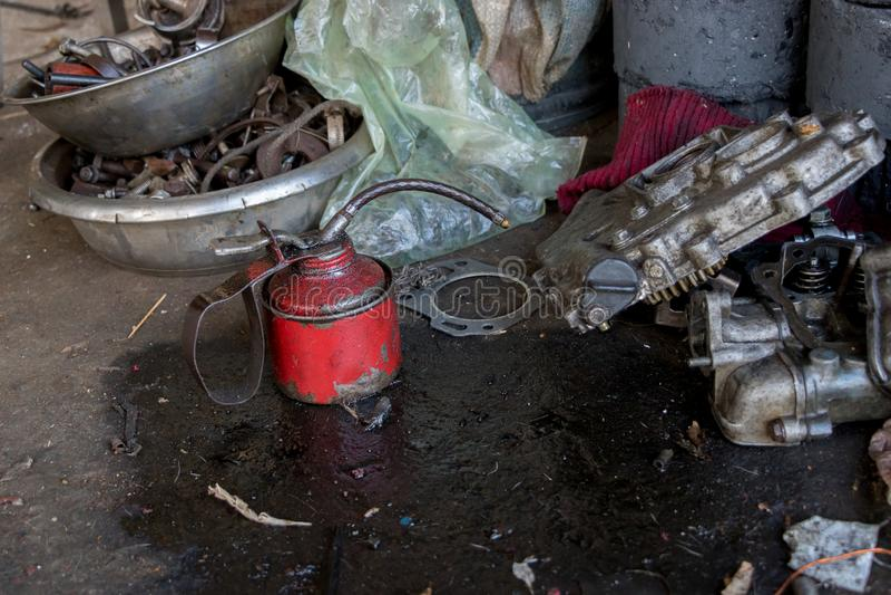 Poder roja del aceite lubricante del vintage con las herramientas grasientas en la tierra concreta sucia - reparación de Eqipment foto de archivo