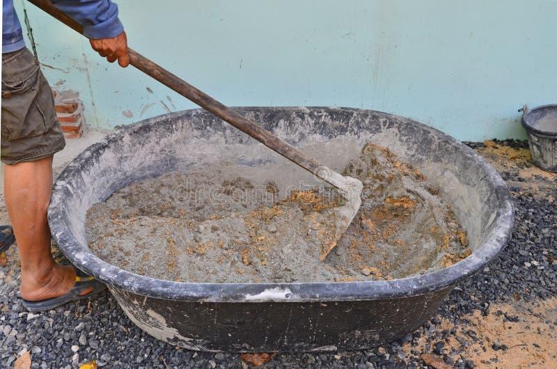 Poder y arena de mezcla del cemento usando la azada en cacerola del mortero imagen de archivo