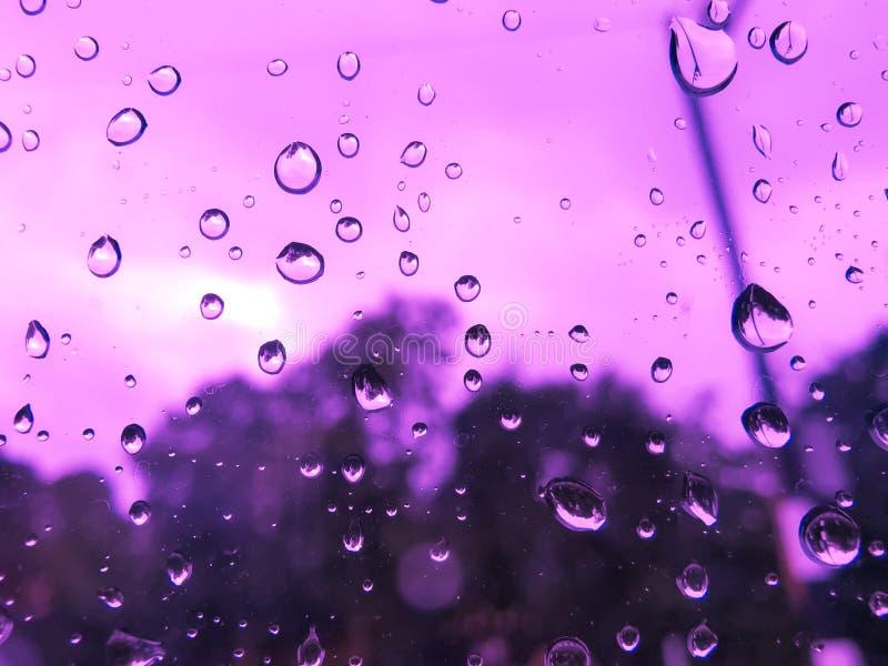 Podeszczowa kropla na nadokiennym samochodzie w purpurach zaświeca plu?ni?cie szklana woda Pora deszczowa, zakończenie w górę obrazy stock