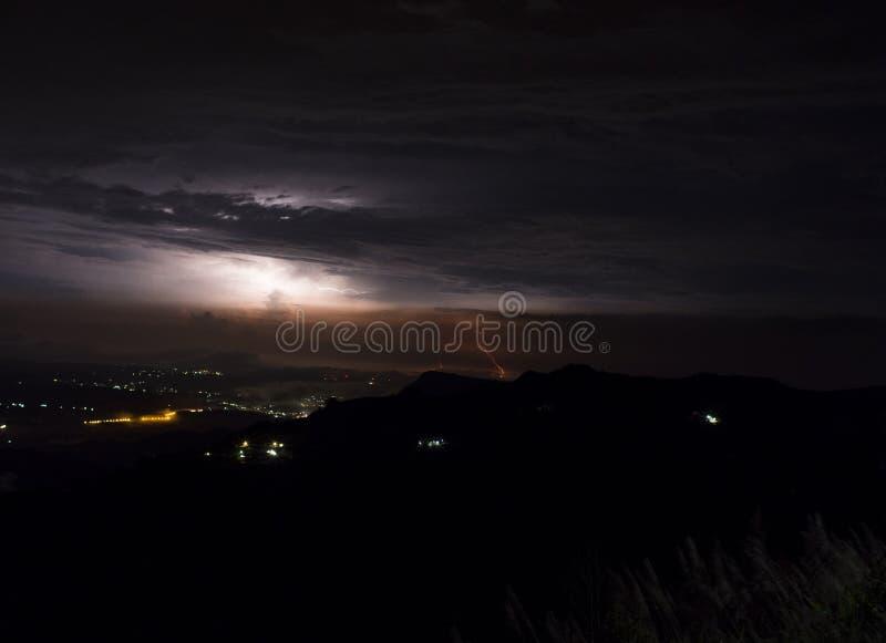 Podeszczowe chmury i burza błyskawicowy rygiel z miastem zaświecają przy nocą fotografia stock